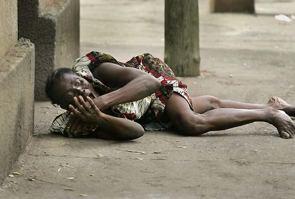 26 abril galeria - madre. La madre de un hombre sospechoso de saqueo se lamente en el suelo mientras un soldado apalea a su hijo. Los poartidarios de la oposición están actuando de forma violenta en las calles erigiendo barricadas y provocando barreras de fuego. El hijo del ex-dictador Gnassingbe Eyadema ha sido el ganador de las elecciones presidenciales en Togo.