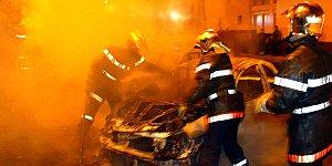 Los bomberos apagan un coche en París (Reuters).