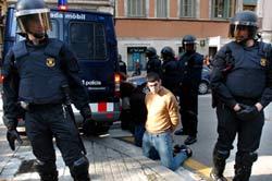 Los agentes custodian a uno de los detenidos tras la manifestación