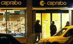 Unos policías mantienen acordonado el supermercado donde se produjo el asalto