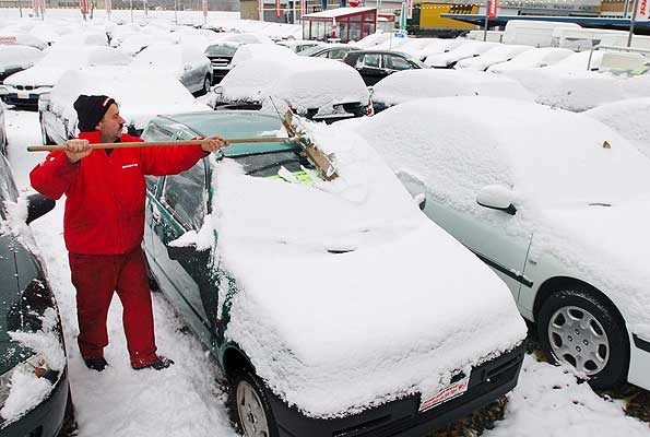251105 - temporal. Hoy empieza el temporal. En la imagen un empleado de un concesionario de coches retira la nieve de los vehículos en Zurich, Suiza.