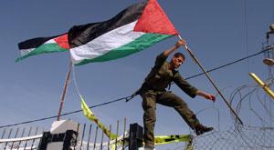 Un miembro de la seguridad palestina coloca una bandera en el paso de Rafah