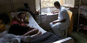 Una enferma de Sida recibe cuidados por parte de un sanitario (EFE).