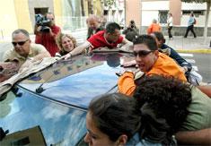 Familiares de la concejala cubren el coche donde viaja la edil (Foto: Efe)