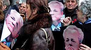 Simpatizantes de Milosevic portan fotos del líder frente a la sede del Partido Socialista Serbio en Belgrado. (EFE)