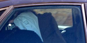 La alcaldesa, se cubre la cabeza en el coche policial (Efe).