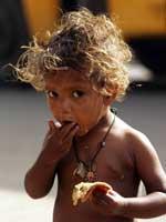 Un niño come sobre el pavimento de una carretera de Nueva Delhi. (Reuters)