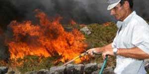 Un hombre colabora en las labores de extinción del incendio que afecta al monte O Pindo, en A Coruña (Efe).
