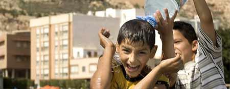 Dos niños se lanzan agua para combatir el calor en Almería (Foto: Efe)