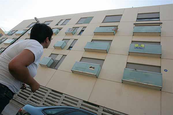 """Un bloque de viviedas con varios carteles de """"Se vende"""" en su fachada"""