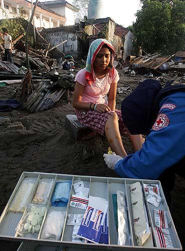 tsunami herida. Un miembro de la Cruz Roja atiende a uno de los heridos en el tsunami, en medio de un paraje destruido por la ola.