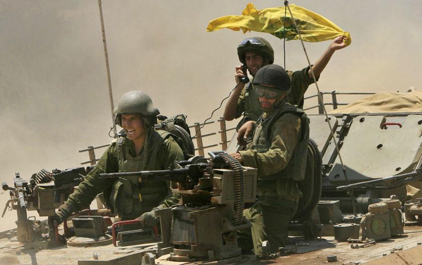 Tres soldados israelíes con una bandera de Hizbulá robada.