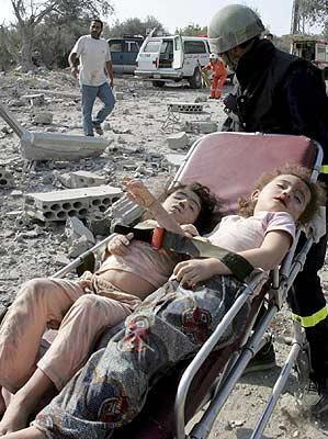 Un trabajador de los equipos de rescate lleva los cuerpos sin vida de dos niñas en una camilla después de un bombardeo en Qana (Efe).