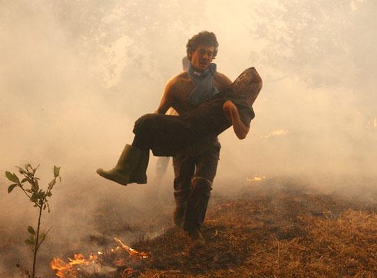 Una señora es llevada en brazos tras ser desalojada de su casa de campo en el incendio forestal en Ponte Romaño, en Santiago de Compostela. (X.Rey / Efe)