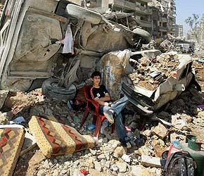 Un joven permanece sentado ante las ruinas de su casa, en Beirut