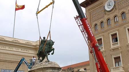 Una grúa comienza a retirar esta mañana la estatua ecuestre del general Francisco Franco que presidía el acceso principal de la Academia General Militar de Zaragoza.