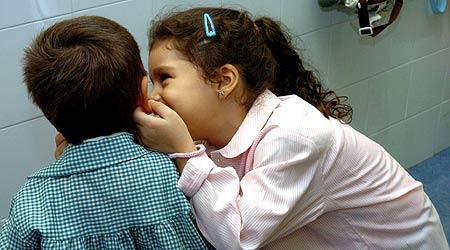 Dos niños cuchichean poco antes de comenzar la clase ayer en el centro escolar José Calvo Sotelo, en Madrid,