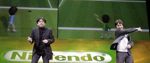 Iwata, presidente de Nintendo y Miyamoto, su director general, muestran cómo se juega al tenis con el nuevo mando de Wii