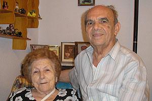 Andrés, junto a su esposa, muestra una foto de sus seis nietos