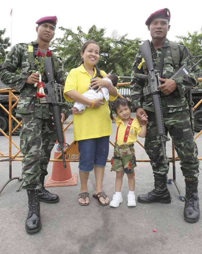 Una familia posa con soldados tailandeses.