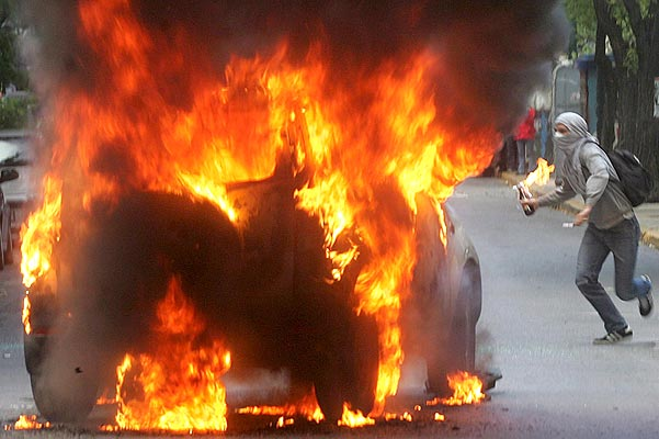 031106 Fuego en atenas. Fuego griego. Un joven lanza una bomba incendiaria a los antidisturbios durante los enfrentamientos en Atenas. Miles de manifestantes se enfrentaron a la policía durante un acto de apoyo a los enseñantes de educación primaria y en protesta contra la política educacional del gobierno.