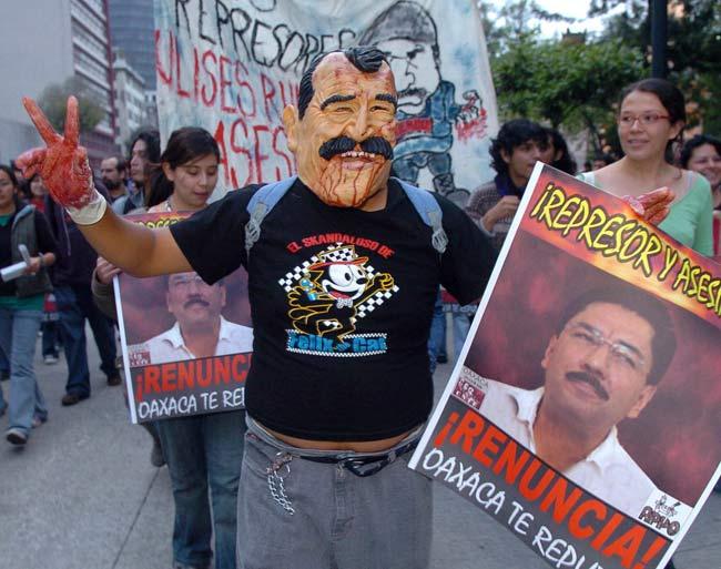 Un manifestante disfrazado de Fox porta un cartel contra el gobernador de Oaxaca.