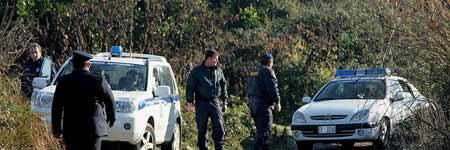 Unos policías examinan el camino rural donde se han encontrado los cadáveres de cinco cazadores.