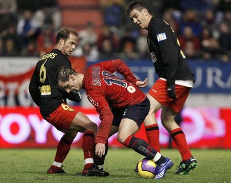 Soldado, del Osasuna, intenta llevarse el balón ante dos jugadores del Mallorca