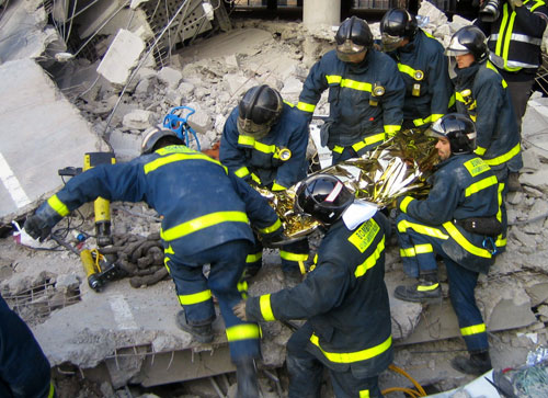 Varios bomberos trasladan el cadáver de Diego Armando Estacio. (Efe)