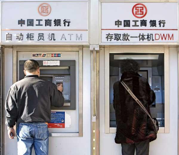 Dos ciudadanos sacando dinero de un cajero automático en Pekín. (Diego Azubel / China)