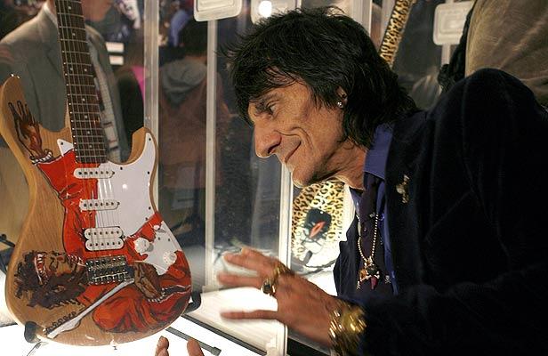 020207 guitarra de rolling stones. El arte del rock. Ronnie Wood posa junto a su guitarra, que él mismo decoró y que forma parte de la exposición Born To Rock: The Life and Times of the Electric Guitar en un local de Harrods en Londres. Consta de unas 150 guitarras, incluyendo The Frying Pan, la primera guitarra eléctrica de la historia.