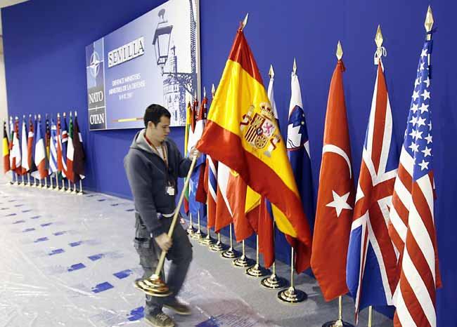 Un operario coloca la bandera de España en el Salón del Palacio de Exposiciones y Congresos de Sevilla