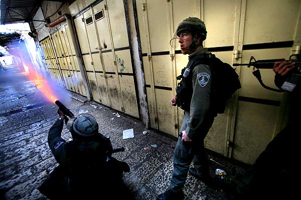 090107 Israelíes haciendo fuego contra palestinos. Enfrentamientos. Un policía israelí arroja bombas de gas a palestinos durante los enfrentamientos en la Ciudad Vieja de Jerusalén. La oración de los viernes en la Explanada de las Mezquitas ha degenerado en disturbios, después de que musulmanes que protestaban por las obras cerca de ese lugar santo lanzaran piedras a agentes israelíes, que respondieron con gases lacrimógenos para evacuar la zona.