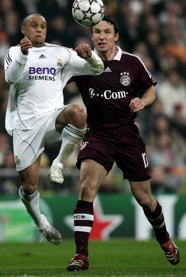 Roberto Carlos y Van Bommel disputan un balón durante el partido