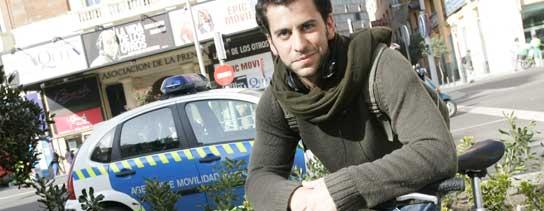 Federico, con su bici, delante de un coche de Policía. (Jorge Paris).