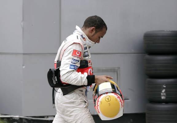 Lweis Hamilton se encamina al 'pit lane' después de sufrir un percance con su coche.