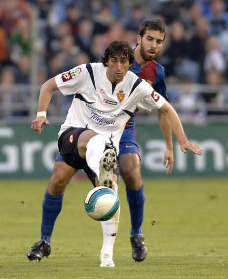 Diego Milito protege el balón ante el acoso de Oleguer.