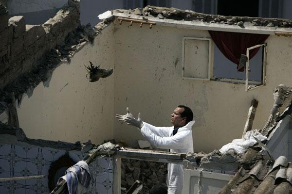 Atentado Casablanca 1. Restos del horror. Un operario de la brigada de explosivos coge una bota de uno de los tres suicidas que se inmolaron en La Fida, Casablanca, causando al menos 15 heridos, tras un tiroteo con la Policía.