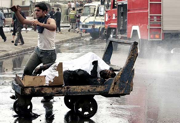 180407 Cuerpos quemados en bagdad, semana. Matanza en Bagdad. Un iraquí recoge el cuerpo quemado de una de las víctimas de la sangrienta jornada en Irak. Más de 160 personas han muerto en cuatro atentados en la capital iraquí.