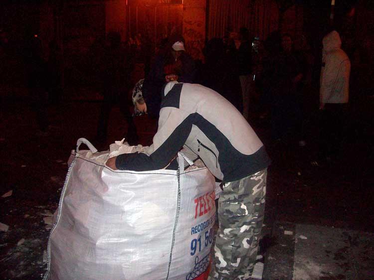 """Batalla campal. """"Se van a enterar"""". En plena calle Fuencarral varios jóvenes recargaban munición en un contenedor de obra. Objetivo, los antidisturbios."""