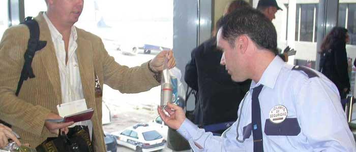 Un agente  de Seguridad revisa los productos líquidos del equipaje de mano.