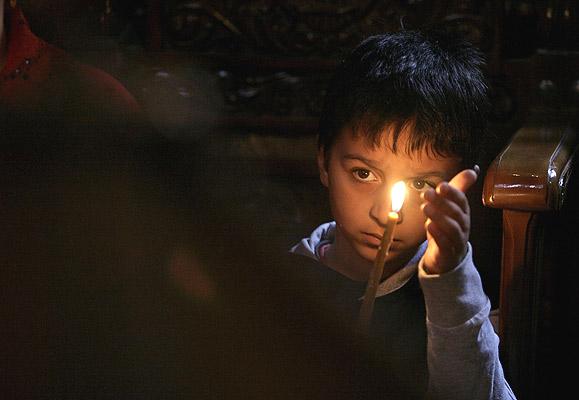 010607 Niño gitano con vela. Iluminado. Un niño de la comunidad gitana sostiene una vela durante una ceremonia religiosa en Bucarest para recordar la deportación masiva 25.000 gitanos de hace 65 años durante la Segunda Guerra Mundial.