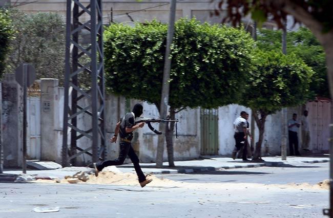 Un miembro del grupo Fatah corre para protegerse durante enfrentamientos contra militantes de Hamas en Gaza