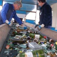Dos operarios apartan lo que no es vídrio en el complejo medioambiental