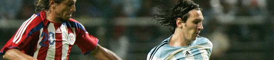 Lionel Messi (dch) se lleva el balón ante el paraguayo Nelson Cuevas