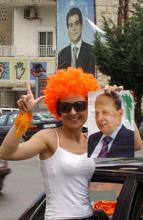 Una mujer libanesa, partidaria del candidato del general opositor Michel Aoun, posa con un cartel de Aoun, frente a un cartel del ministro asesinado Pierre Gemayel
