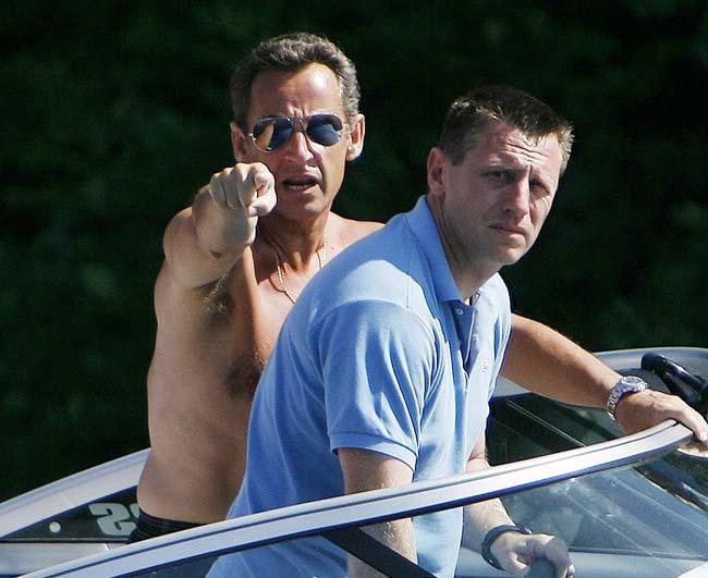 El presidente francés, Nicolas Sarkozy, señala a los fotógrafos, con gesto molesto, durante un paseo por el lago Winnipesaukee