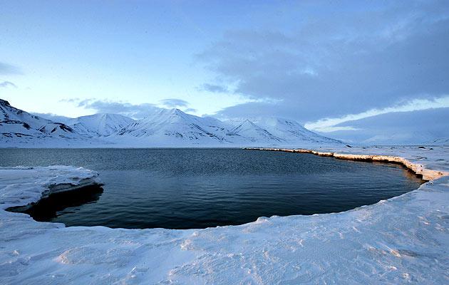 La luz del sol ilumina la medianoche en un fiordo cerca del pueblo noruego de Longyearbyen