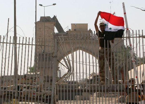 Un soldado iraquí enarbola la bandera de su país en el Palacio de Basora (Reuters)