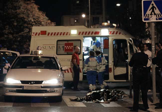 Facultativos del SUMMA y agentes de la Policía Nacional, junto al cuerpo sin vida del taxista apuñalado en su propio vehículo